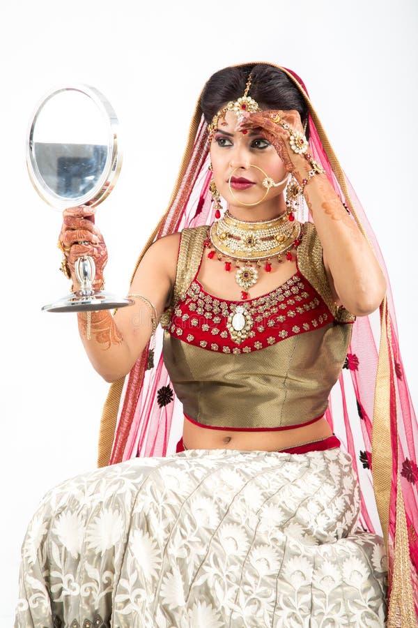 Sposa indiana che controlla il suo trucco nello specchio immagini stock libere da diritti