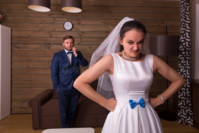 Sposa insoddisfatta, sposo che parla sul telefono immagine stock libera da diritti