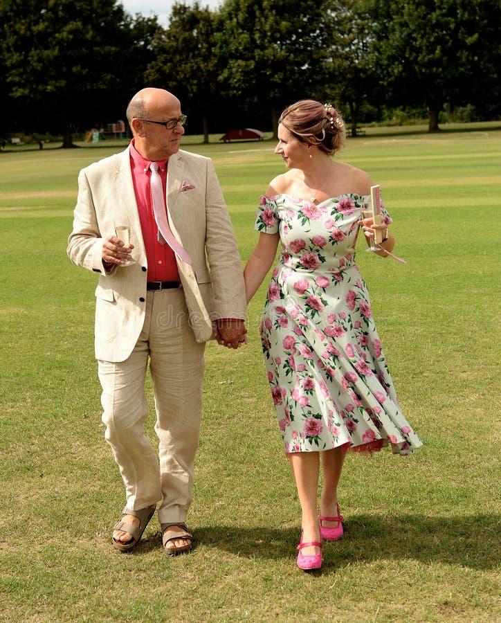 Sposa matura e sposo che camminano sull'erba fotografia stock