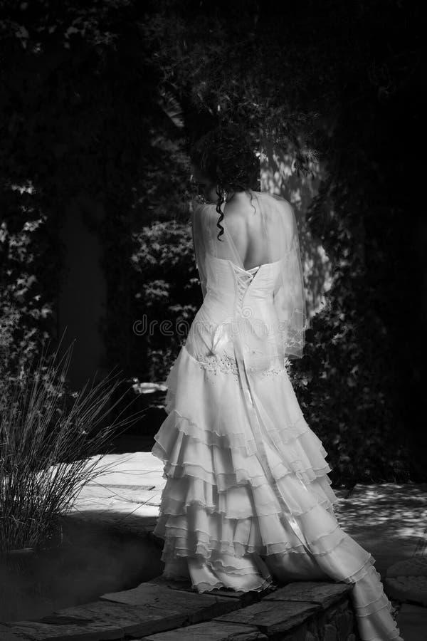 Sposa monocromatica accanto alla fontana fotografia stock