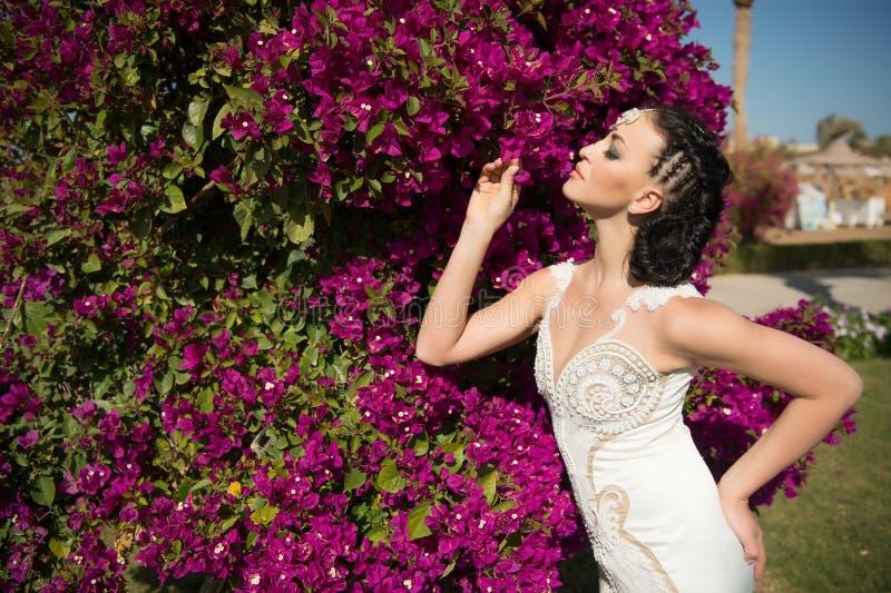 Sposa sensuale in vestito bianco il giorno di estate Posa della donna con i fiori sboccianti Modello di moda con capelli castana  fotografia stock libera da diritti