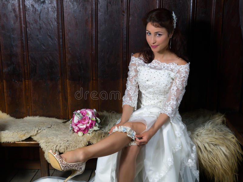 Sposa sexy che mette su una giarrettiera fotografie stock libere da diritti
