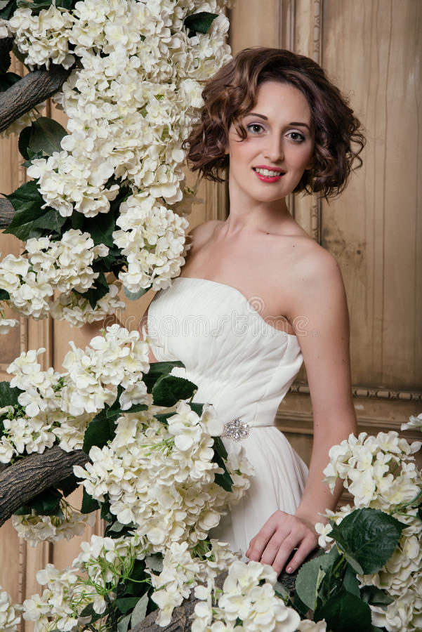 Sposa sorridente circondata dai fiori bianchi fotografie stock