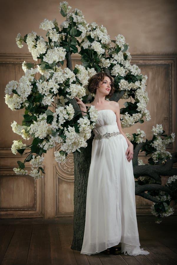Sposa sorridente vicino all'albero con i fiori bianchi fotografie stock
