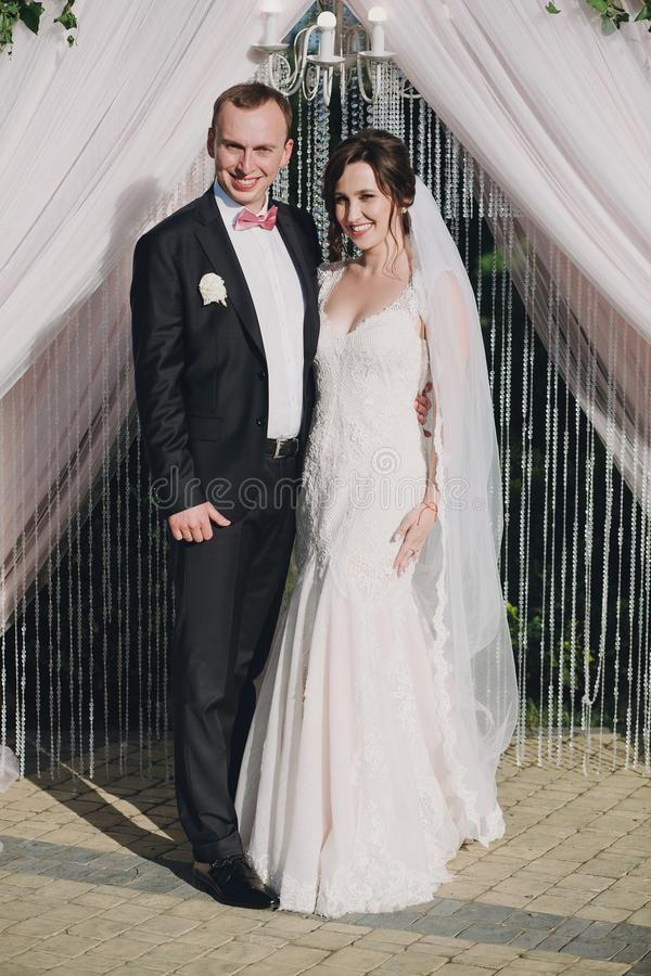 Sposa splendida e sposo alla moda che posano all'arco alla moda di nozze al ricevimento nuziale in ristorante Sorridere di lusso  immagine stock libera da diritti