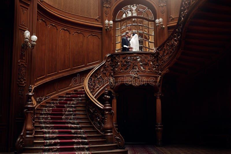 Sposa splendida elegante e sposo alla moda che stanno sullo stai di legno immagini stock libere da diritti