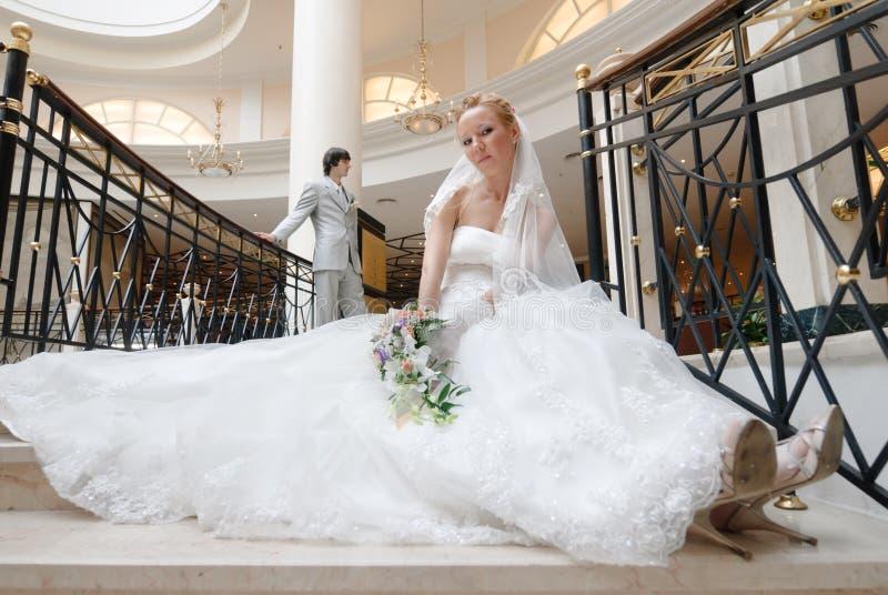 Sposa sulla scala. Su priorità bassa è lo sposo fotografia stock