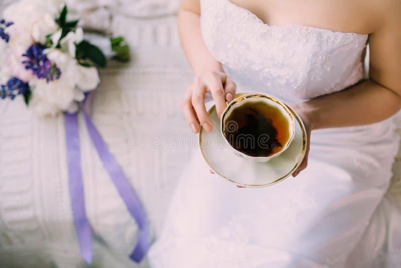Sposa tenera sexy in vestaglia o vestito da sposa con decollete bevendo una tazza del tè nero di mattina in tazza della porcellan fotografia stock libera da diritti