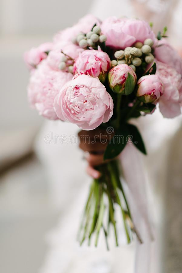 Sposa in un vestito da sposa che tiene un mazzo di nozze in suo primo piano delle mani fotografie stock