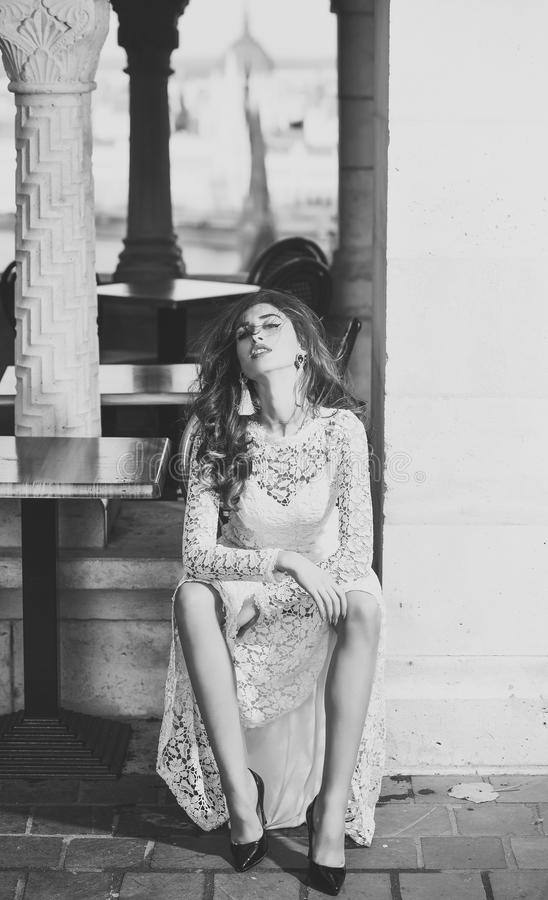 Sposa in un vestito da sposa Ragazza con capelli castana lunghi, bellezza La donna sexy si siede da solo in caffè della via Donna fotografia stock libera da diritti