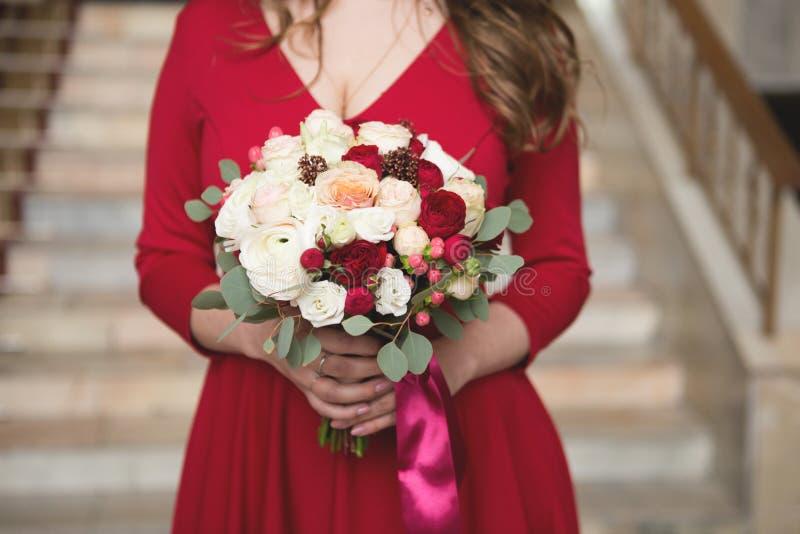 Sposa in un vestito rosso Damigella d'onore in un vestito rosso Mazzo di nozze con un nastro rosso fotografie stock libere da diritti