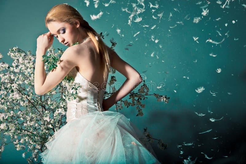 Sposa in vestito da sposa dietro il cespuglio con i fiori immagine stock