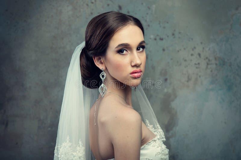 Sposa in vestito da sposa ed in velo fotografia stock