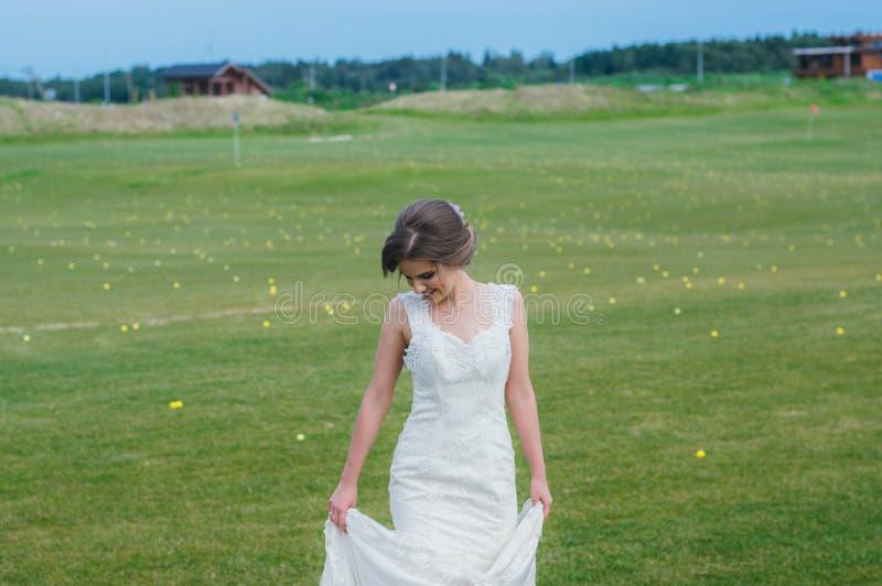Sposa in vestito da sposa sul campo verde del club di golf fotografia stock