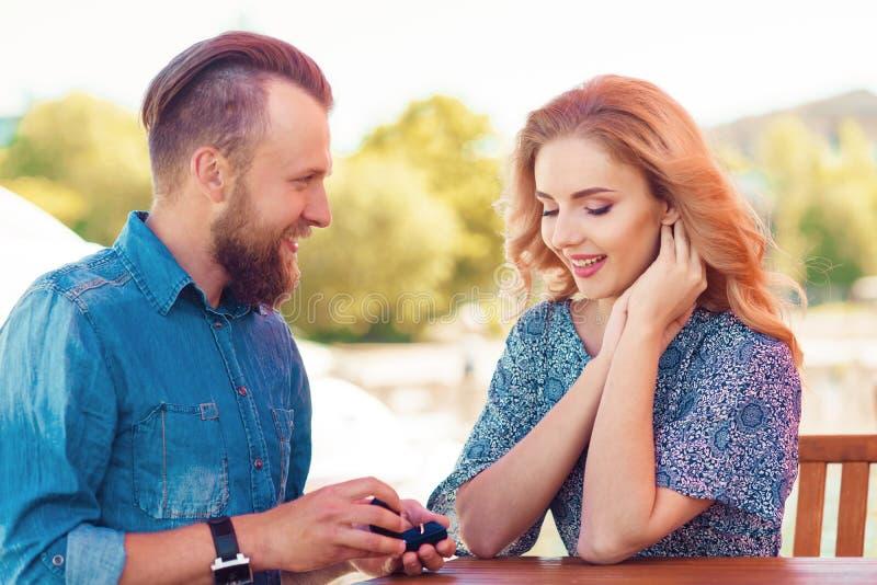 Sposimi concetto Coppie di amore che ottengono impegnate in un caff? all'aperto Priorit? bassa di autunno fotografia stock