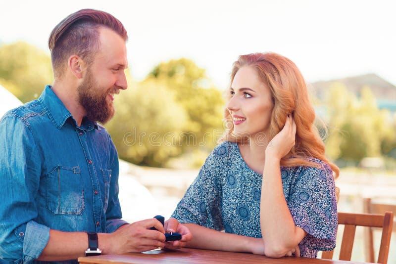 Sposimi concetto Coppie di amore che ottengono impegnate in un caff? all'aperto Priorit? bassa di autunno fotografia stock libera da diritti