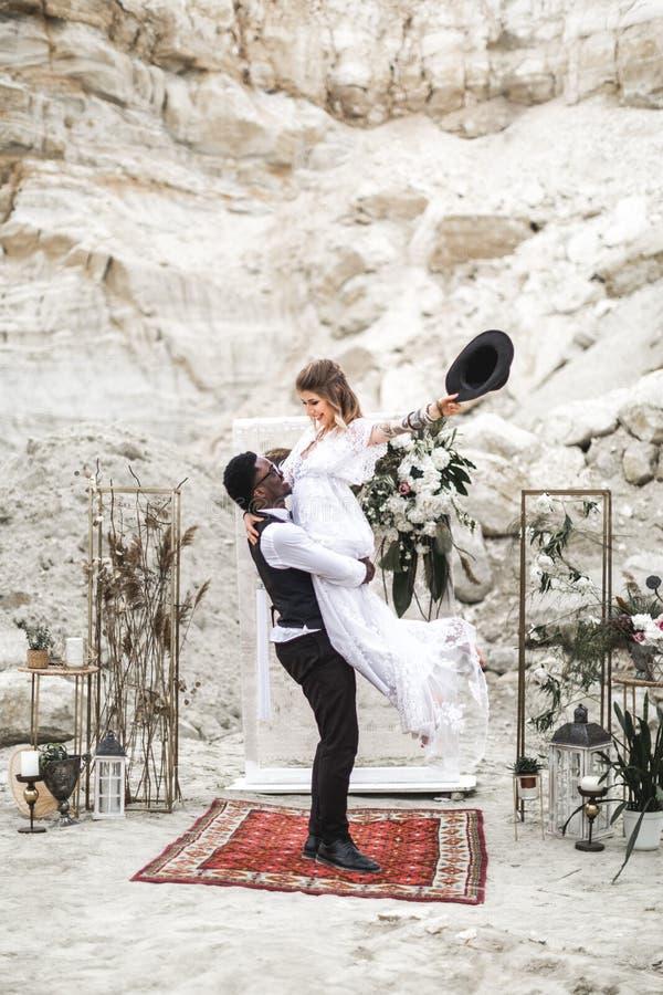 Sposo africano e sposa caucasica che si abbracciano in uno stile di boho prima dell'arco di nozze dai fiori freschi governi immagini stock libere da diritti