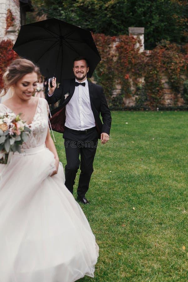 Sposo alla moda che corre sotto l'ombrello in all'aperto piovoso a Gorgeou immagini stock libere da diritti