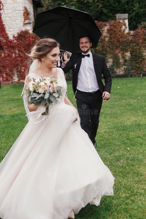 Sposo alla moda che corre sotto l'ombrello in all'aperto piovoso a Gorgeou immagine stock libera da diritti
