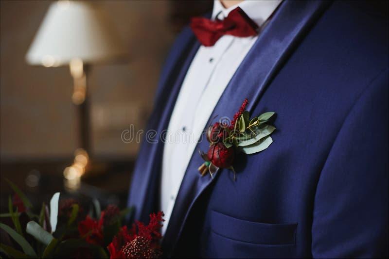 Sposo alla moda in vestito blu con la cravatta a farfalla rossa ed il boutonniere verde-rosso sul suo rivestimento - dettagli di  fotografia stock