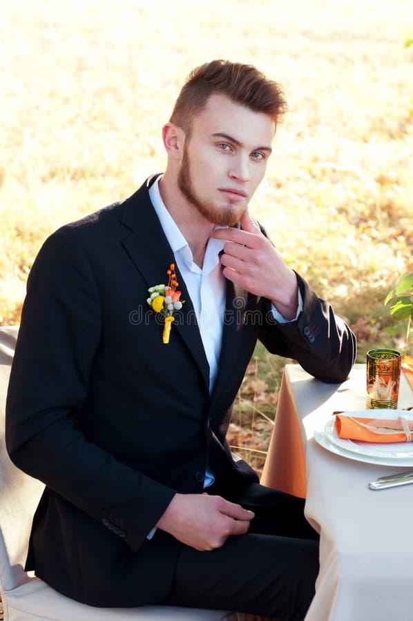 Sposo bello che si siede alla tavola di nozze Ritratto esterno fotografie stock libere da diritti