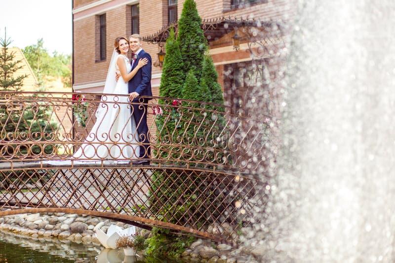 Sposo bello e sposa attraente che abbracciano mentre stando sul Br immagini stock