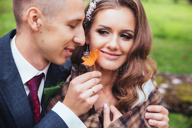 Sposo che abbraccia la sua sposa in parco Coppie di cerimonia nuziale immagini stock libere da diritti