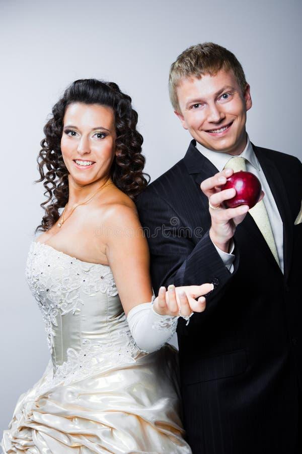 Sposo che cattura mela rossa dalla bella sposa fotografia stock