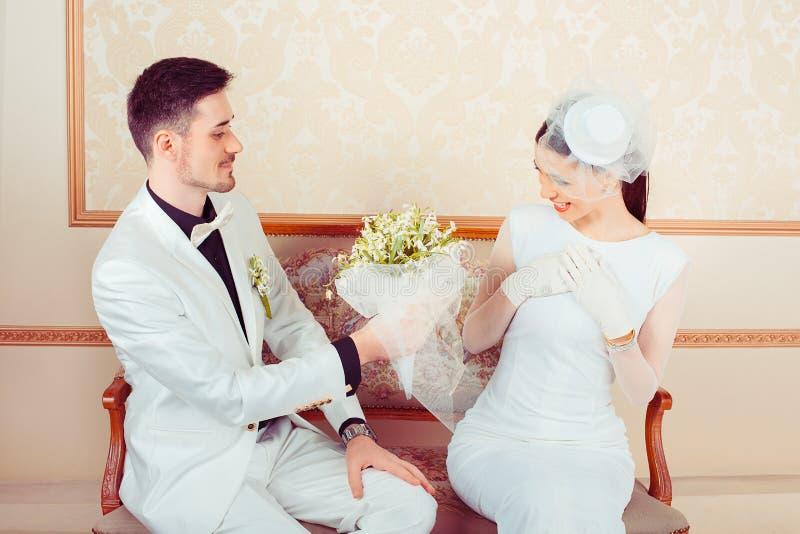 Sposo che dà mazzo alla sposa incantante immagine stock