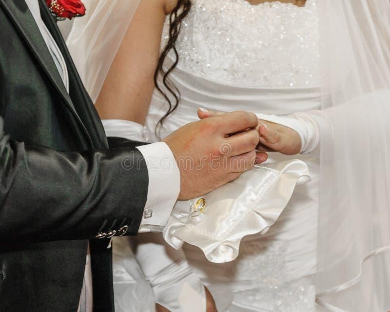 Sposo che mette l'anello di oro fotografia stock