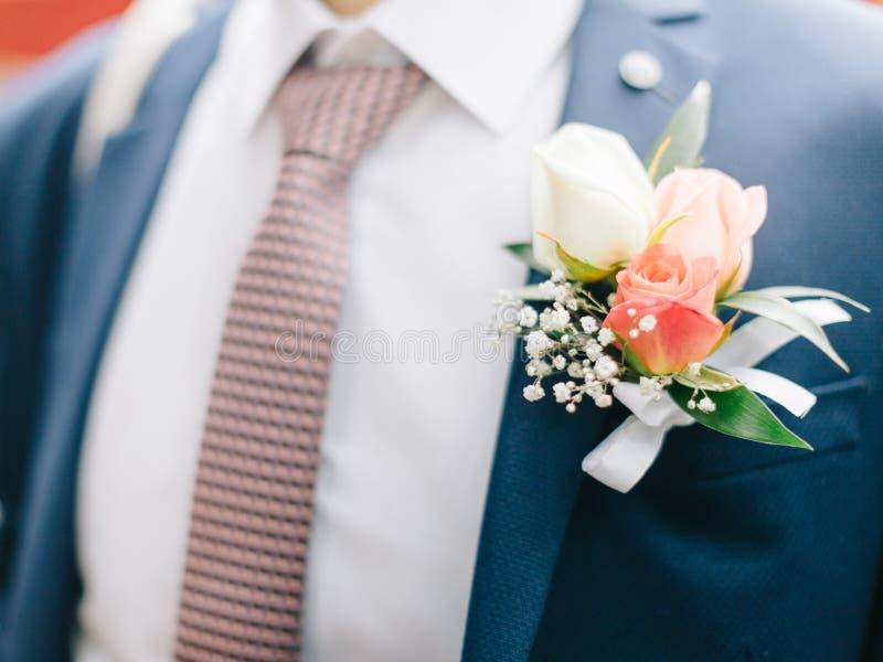 Sposo che organizza boutonniere di rosa fotografie stock