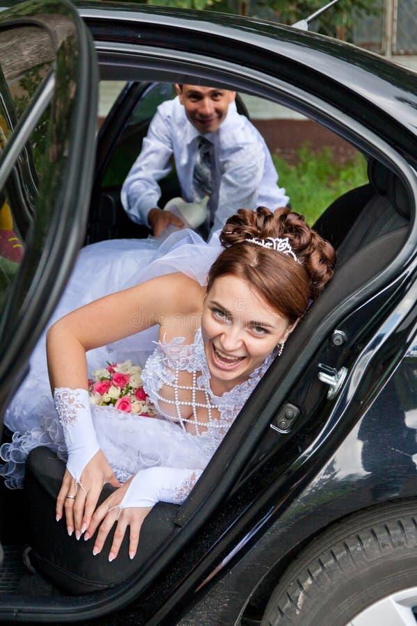 Sposo che prova a trascinare la sposa dall'automobile immagine stock