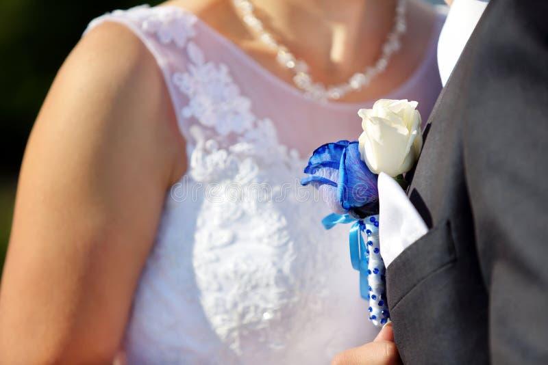 Sposo con l'occhiello della rosa del blu di nozze all'aperto immagine stock