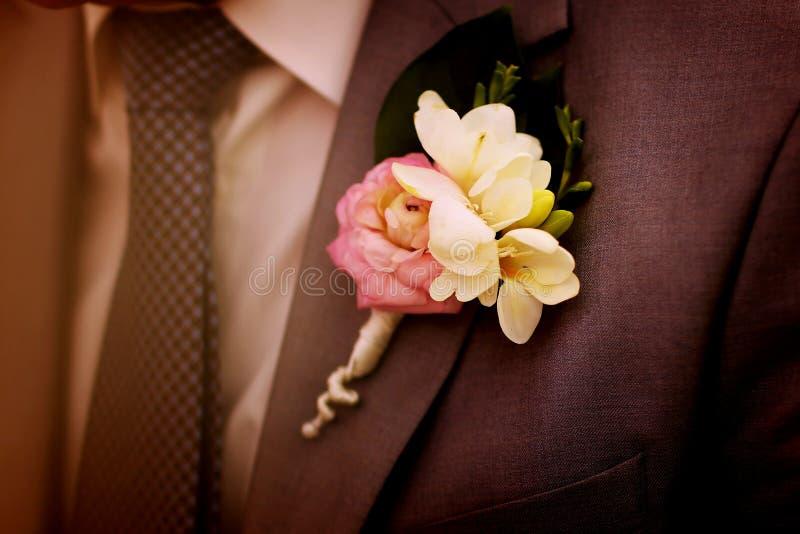 Sposo del vestito del primo piano con l'occhiello tenero del fiore immagini stock