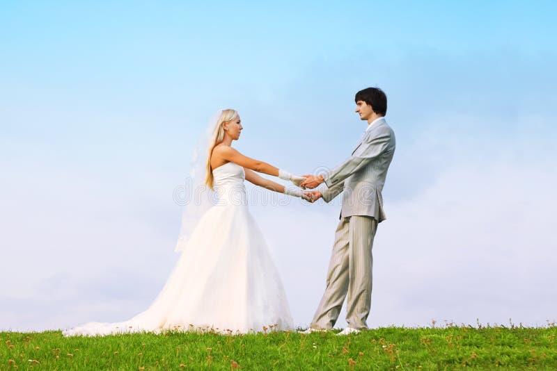 Sposo e sposa che si levano in piedi sull'erba verde fotografia stock