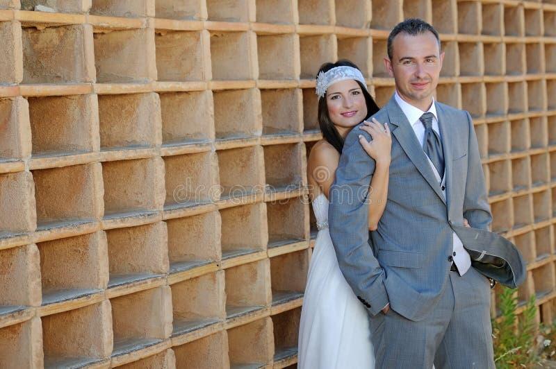 Sposo e sposa dietro la presa lui dalla spalla immagine stock libera da diritti