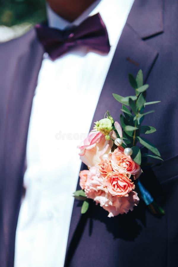 Sposo elegante vestito in vestito porpora e camicia bianca decorazione di nozze su un rivestimento fotografie stock
