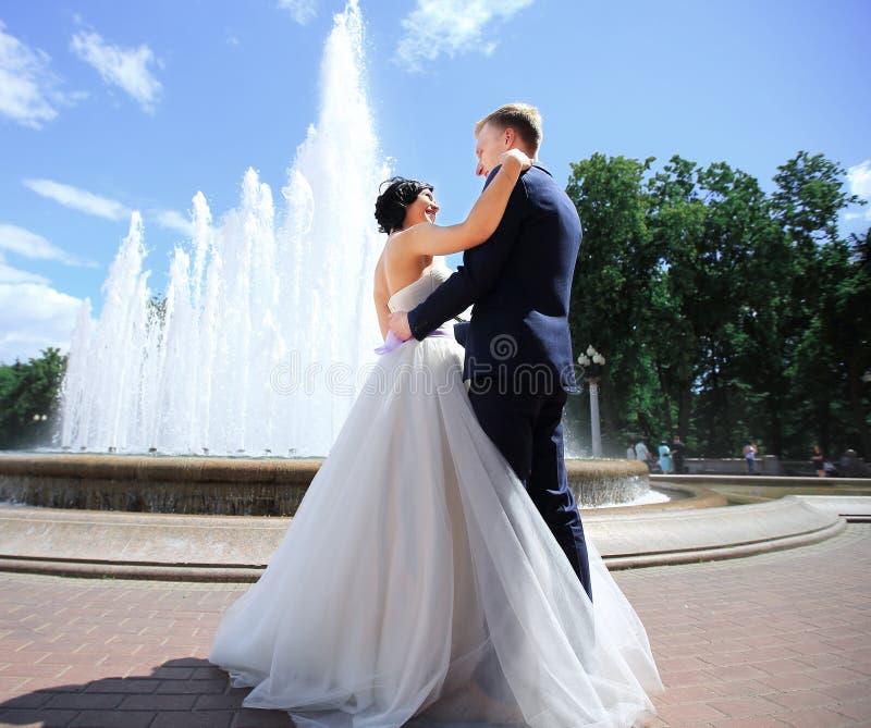 Sposo Enamoured e la sposa contro una fontana immagini stock