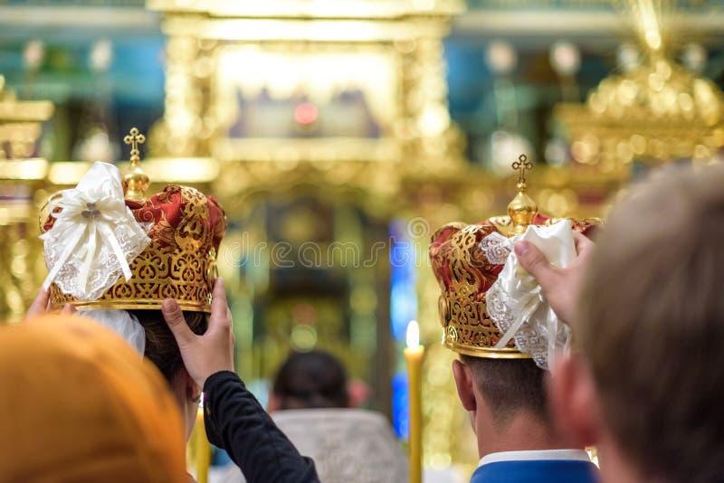 Sposo felice della sposa in corone a cerimonia di nozze in chiesa immagine stock