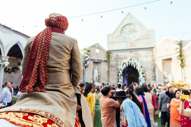 Sposo indiano che sbarazza cavallo bianco al posto di cerimonia di nozze con gli ospiti a Bangkok, Tailandia fotografia stock