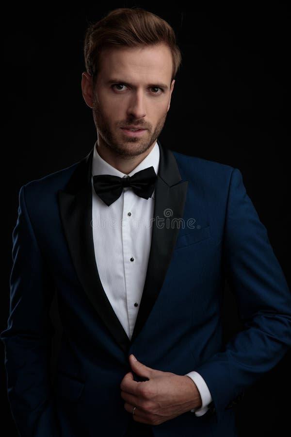 Sposo motivato che sbottona il suo smoking blu fotografia stock