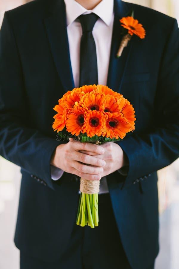 Sposo nel mazzo blu di nozze della tenuta del vestito dei fiori in mani fotografia stock libera da diritti