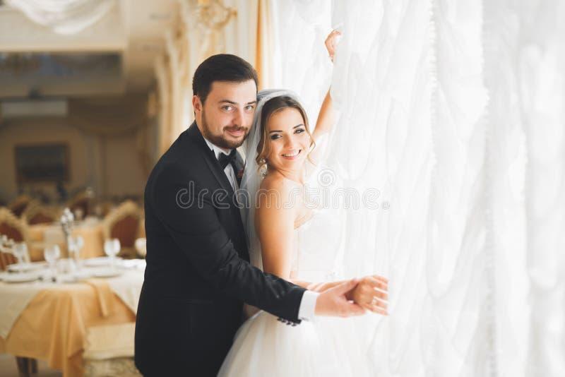 Sposo splendido che abbraccia delicatamente sposa alla moda Momento sensuale delle coppie di lusso di nozze fotografie stock