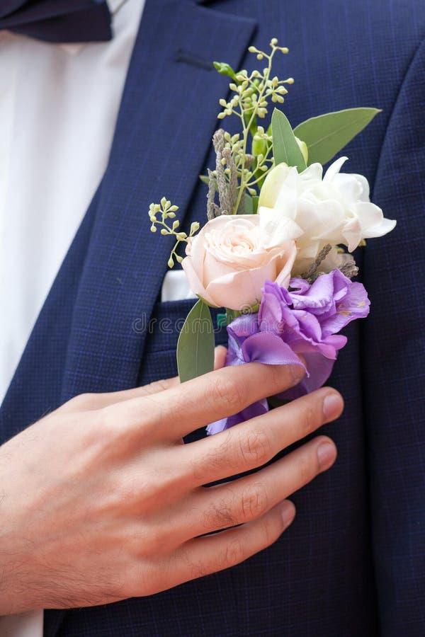 Sposo in un occhiello della tenuta del vestito immagini stock libere da diritti