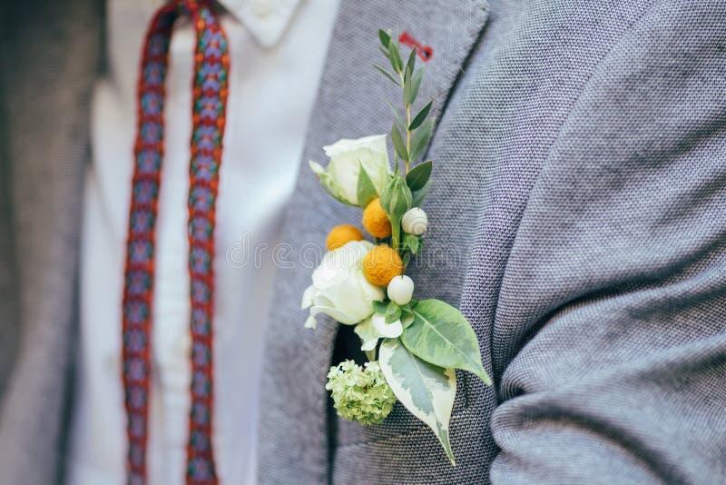 Sposo in un occhiello della tenuta del vestito immagine stock