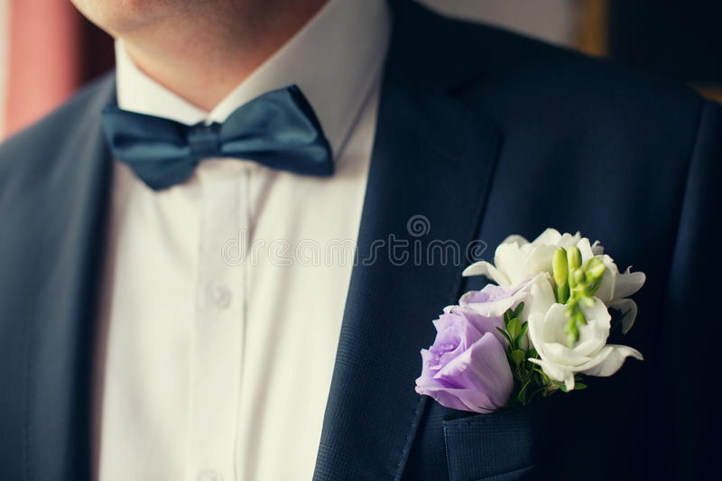 Sposo in vestito nero con l'occhiello del fiore fotografia stock
