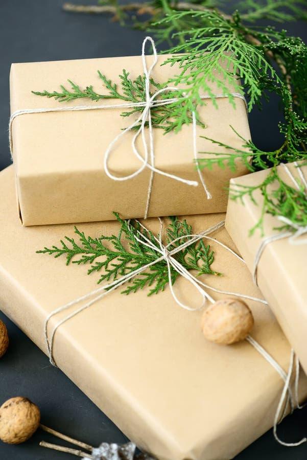Spostamento dei pacchetti rustici di Natale di eco con carta marrone, corda ed i rami naturali dell'abete su fondo scuro immagine stock libera da diritti