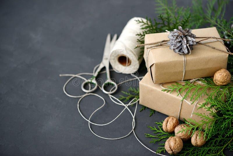 Spostamento dei pacchetti rustici di Natale di eco con carta marrone, corda ed i rami naturali dell'abete su fondo scuro fotografie stock libere da diritti
