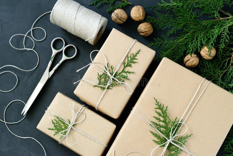 Spostamento dei regali rustici di Natale di eco con la carta del mestiere, la corda ed i rami naturali dell'abete su fondo scuro immagine stock