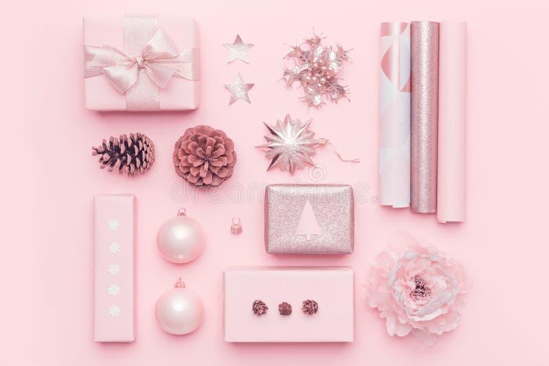 Spostamento di regalo Regali nordici rosa di natale isolati sul fondo di rosa pastello Scatole avvolte di natale immagine stock